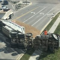 Truck flipped over in accident with spilt gravel material